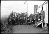 [Group posed beside the Covenant Church including Rev. and Mrs. Axelson.]