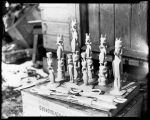 [Carved wooden knives, spoons, candlesticks, totems, etc. Standing on a wooden crate.]
