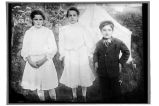 [Three nicely dressed children, one boy and two girls, standing outside in front of tent.]