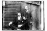 [Two nicely dressed men posing outside of a wooden structure.]