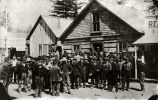 "[Group of men in front of log building identified as ""City Hall"".]"