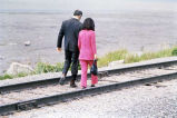 [Gov. and Mrs. Hammond, walking on railroad tracks; back to camera.]