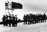 Coast Guard color guard and the crew of the Cutter Liberty march to the Liberty.