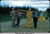 Maynard Dahlstrom and 2 friends posing with highway sign.