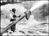 Man at nozzle of placer hose spouting water, Dawson.