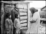 [Older woman interacting playfully with two boys and a man as they stand at entrance to log...