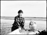 [Man with small Johnson outboard  motor boat]