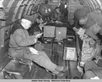 Major General Buckner and two crewmen, supplies and mail in flight over Aleutians, 1943.