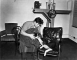 [Thornton holding puppy in coat with dog on chair licking puppy.]