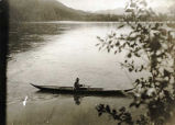 Indian in birch bark canoe, Yukon River, at Eagle.