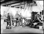 [Interior view of the cannery, showing machine and men working.]