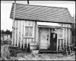 [George Marks, old timer standing in front of a shack at the lagoon.]