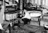 Mayuk. [Native man inside home].