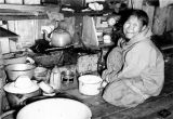 SUNONAGAZUK. [Native woman inside home].