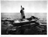 Man holding harpoon and standing on top of kyak [kayak].