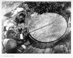 Eskimo beating large drum with stick.  [The Drummer- Nunivak.]