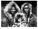 Portrait of man, woman and child wearing fur hooded parkas.