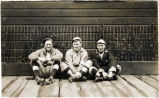 [3 Baseball players sitting on board walk.]