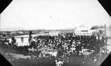 [Town scene along river with bridge, buildings and crowds of people; July 4th in Fairbanks.]