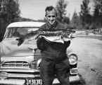[Father Hubbard holding Lake Teslin Trout by car]