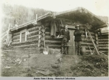Prospectors in front of log cabin.