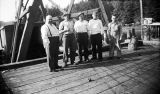 [Five men standing on dock.]