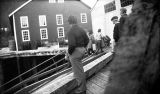 [People on dock, ladies coming up ramp, cannery buildings in background.]