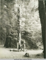 Couple with totem in Lover's Lane, Sitka National Park, Sitka, Alaska.