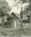 Man and woman with Golden North Hotel buggy among a totem pole and cabin, Skagway, Alaska.