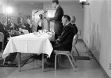 [Senator John Kennedy at indoor venue standing at podium placed on banquet table delivering...