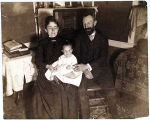 [A couple poses seated with their baby.]