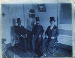 [3 men pose in top hats seated on wooden chairs in the corner of a room.]