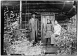 Three people on porch of log cabin.