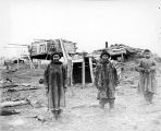 [Two Eskimo women and an Eskimo boy standing near entrance to underground dwelling; cache, left...