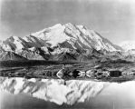[Man looking into water which reflects him and the mountain behind him.]