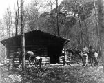 [Men and horses outside a log cabin.]