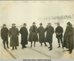 Eight men in heavy coats standing in the snow.