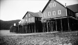 [View from shore of cannery buildings on pilings.]