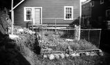 [Fenced in garden area beside building.]