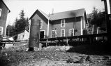 [Man standing on boardwalk; cannery building behind; large chimney-like, barrel structure in...