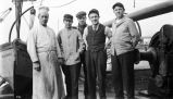 """Aboard the SS DORA"" [Five men standing on deck of boat, possibly crew, one appears to..."