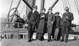 [Three men and two women standing on ship deck.]