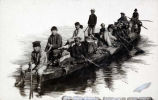 [Thirteen native men and boys paddling low, fully loaded boat.]