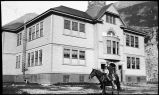 [School building, man and child on horse.]