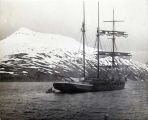 [Sailing ship in water with skiff; snowy mountain, background.]