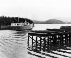 [Ferry sailing by pier covered in stacks of wooden planks.]
