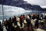 [Ferry passengers view glacier from deck.]