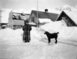 [Man in long fur coat and dog in snowy street; sign on building: Danz Bros. Inc.]