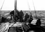 [Four men working on deck of rescue ship.]