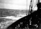 [View over ship's rail to small boat in rough seas.]